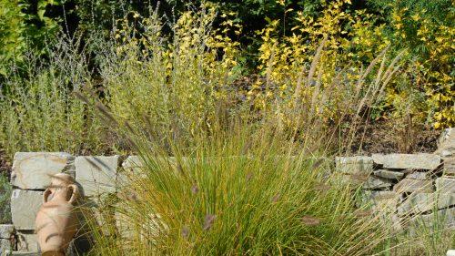Gräser vor der Natursteinmauer