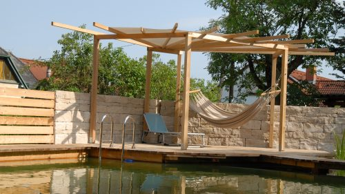 Pergola, Hängematte, Steinmauer und Wasser zum Schwimmen